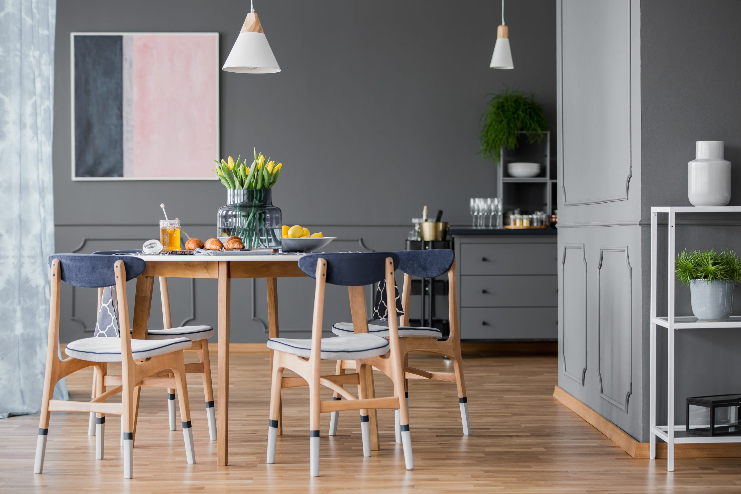 Wooden, paint-dipped chairs around a small dining table with pastries and an abstract painting on a gray wall of a dining room interior with plants
